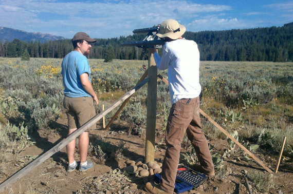 Joe and Daniel affixing hardware that will hold solar panel to post. *Note: wooden stakes had been used to prop up pole while cement dried.*
